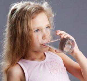 Bambina si disseta sorseggiando un bicchiere di acqua fresca