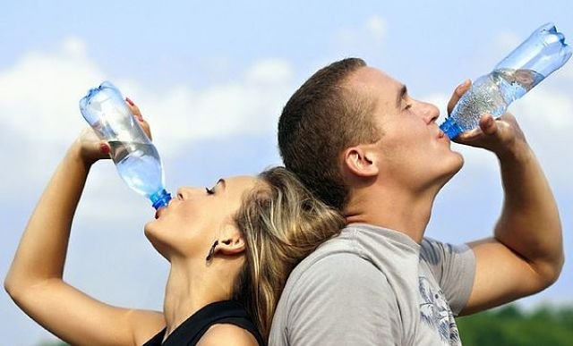 Uomo e donna bevono acqua con piacere per idratarsi