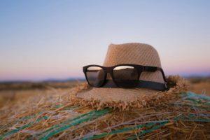 Occhiali da sole e cappello di paglia da indossare per difendersi da raggi solari e afa