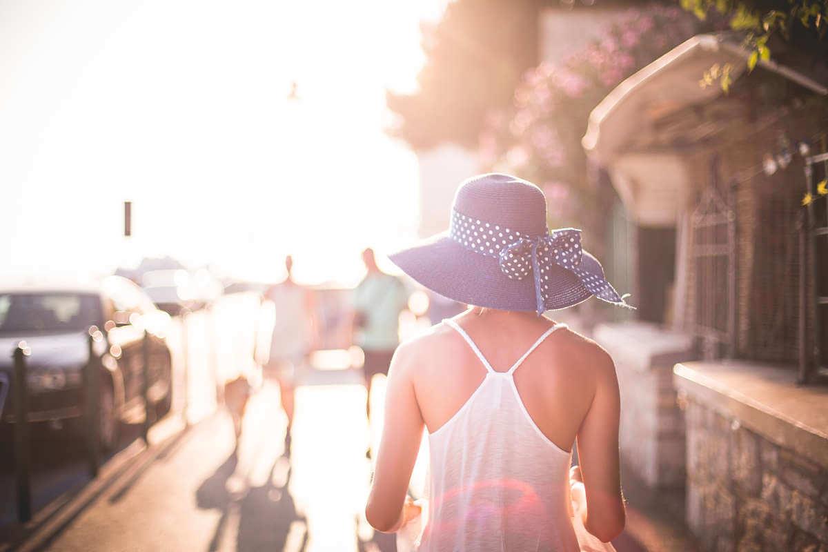 Donna indossa cappello e abito leggero per combattere il caldo afoso