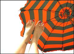 Piedi ben curati sotto l'ombrellone al mare