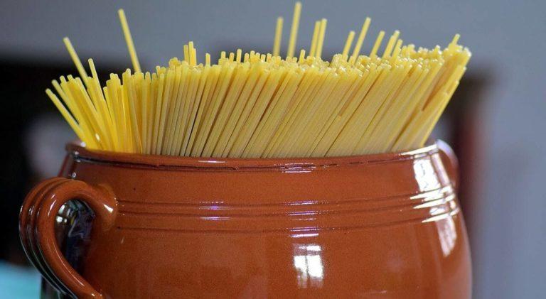 Pentola di terracotta con dentro spaghetti crudi
