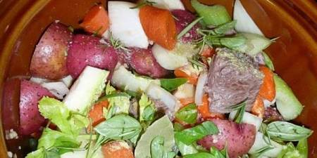Pentola di terracotta contenente carne e verdure da cuocere