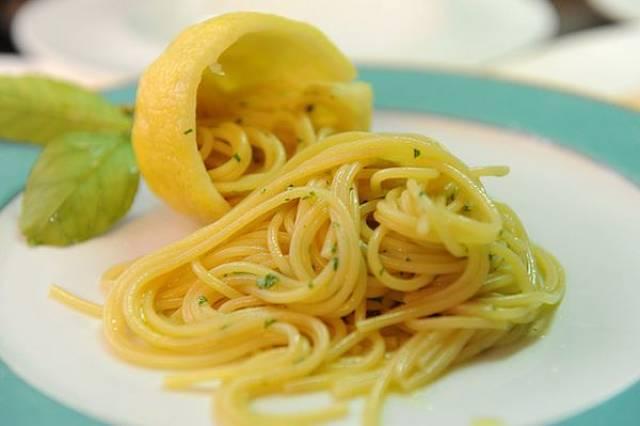 Spaghetti al limone serviti con basilico e buccia del frutto per decorazione