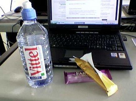 Bottiglietta di acqua accanto al computer portatile