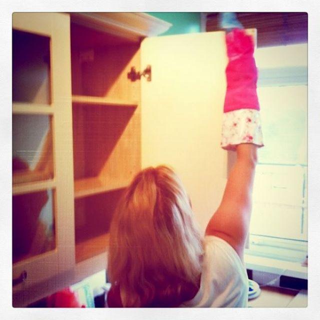 Donna pulisce l'interno del pensile di cucina