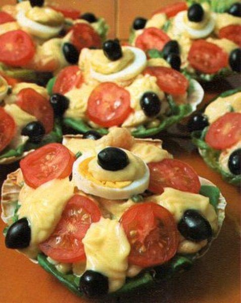 Conchiglie di pesce con guarnizione di maionese, olive e pomodori