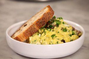 Uova strapazzate con verdure, asparagi, erba cipollina e pane abbrustolito