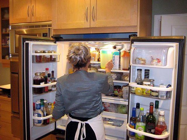 Immagine di donna davanti a frigorifero pieno di cibi