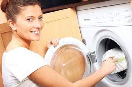 Donna inserisce nella lavatrice biancheria protetta dalla rete