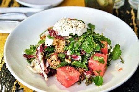Fotografia d'insalata con crostini, anguria e mozzarella