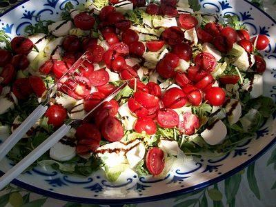 fotografia di piatto con bocconcini di mozzarella, pomodorini, insalata.