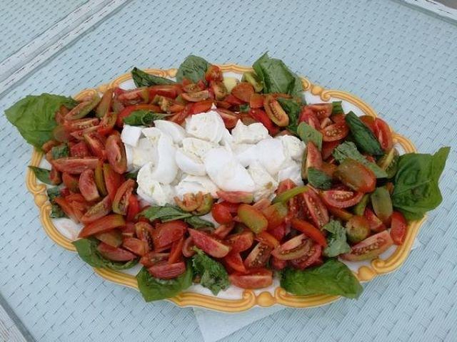 Fotografia di mozzarella contornata da insalata di pomodori e basilico