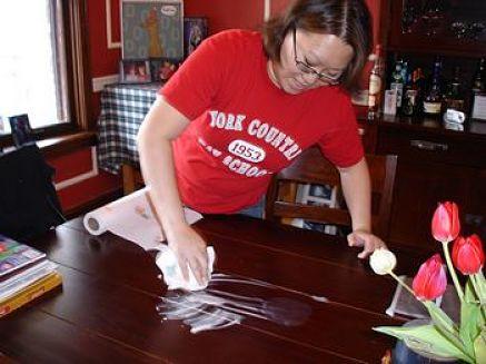 Donna usa la maionese per smacchiare un tavolo di legno