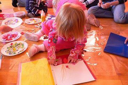 Bambina disegna coi pastelli di cera su pavimento protetto dal nylon