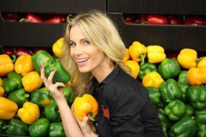 Giovane donna sceglie i peperoni migliori al mercato