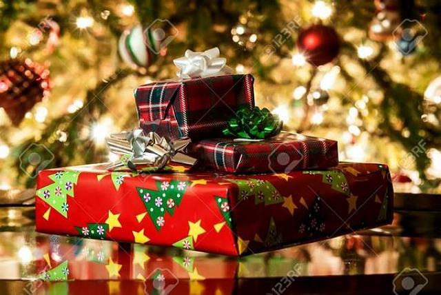 Doni natalizi entro10 euro ben fasciati sotto l'albero ornato