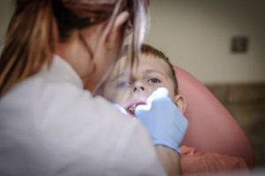 Assistente odontoiatrica esamina la bocca di un bambino