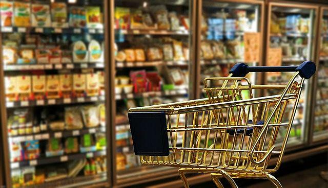 Carrello davanti al frigorifero dei supermercato con prodotti di Private Label nei ripiani bassi