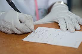 Dottore redige ricetta con indicazioni sui farmaci da assumere