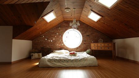Camera da letto in mansarda con soffitto in legno coibentato