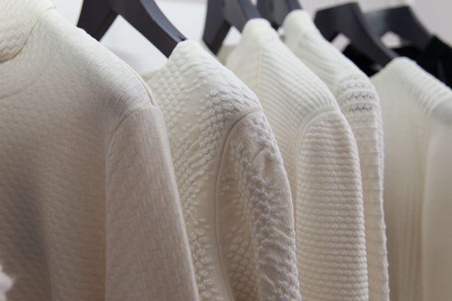 Golf di lana perfettamente sbiancati appesi sulle grucce