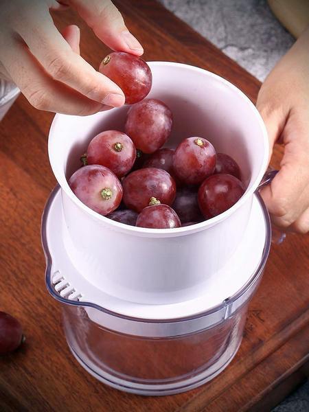 Acini d'uva messi nel pratico estrattore manuale per poi estrarne il succo facilmente