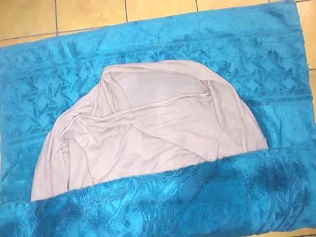 Come arrotolare un pullover di lana nell'asciugamano per eliminare l'acqua in eccesso del lavaggio