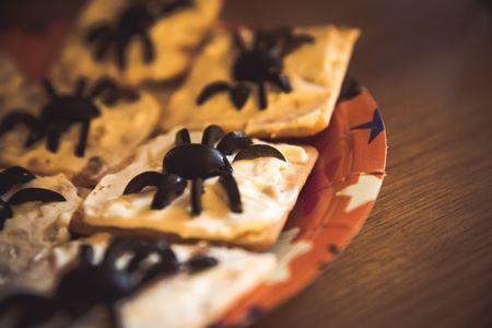 Crackers spalmati di formaggio con decorazione di olive nere a forma di ragno