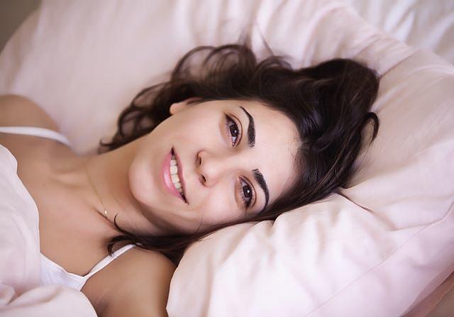 Donna sorridente al risveglio su un cuscino adatto a lei