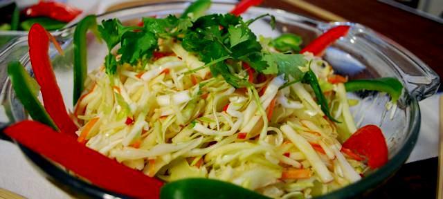 Insalata cruda di cavolo, porri e carote in agrodolce decorata con falde di peperoni