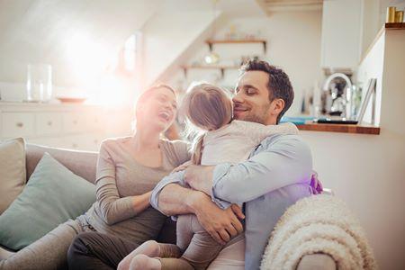 Genitori e figllia sorridenti sul divano