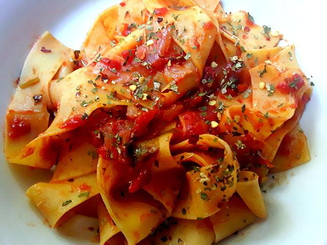 Sfiziose pappardelle con salsa di pomodoro all'origano e peperoncino nel piatto