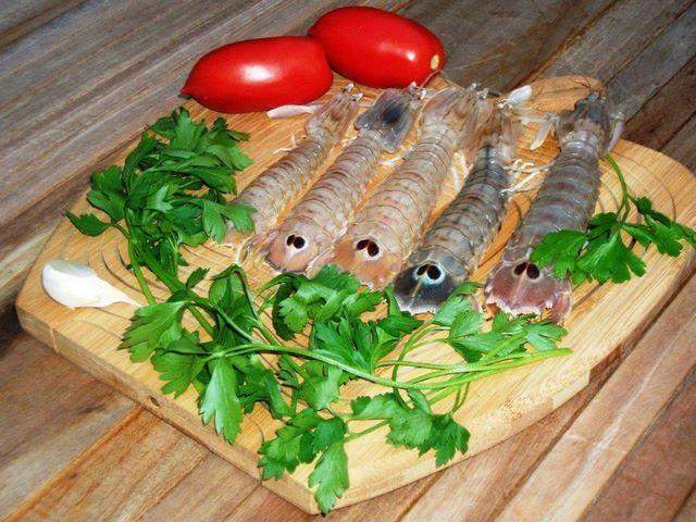 Tagliere con canocchie crude, aglio, pomodori e prezzemolo
