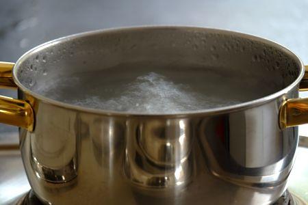 Acqua bollente nella pentola sul fuoco