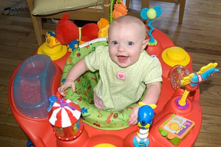 Bebè di 5 mesi gioca nella sdraietta con balocchi adatti alla sua età