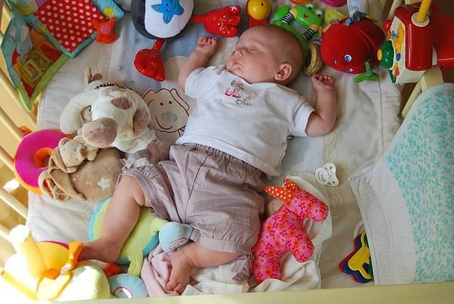 Bebè dorme tra giochi per neonati sicuri e colorati