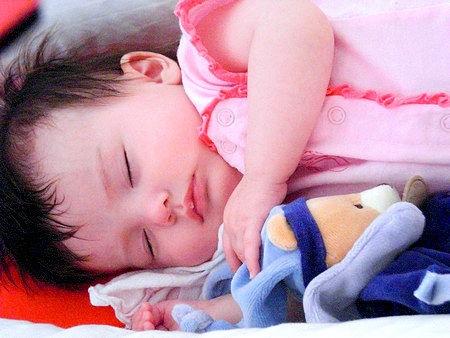 Neonata dorme con il suo animale di peluche doudou