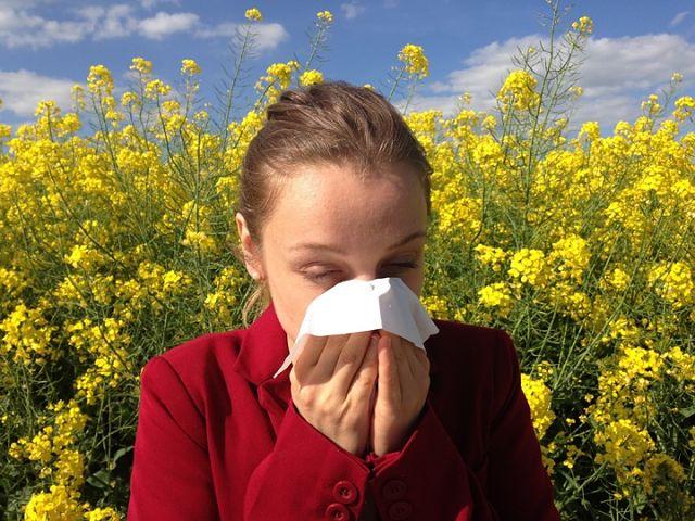 Donna allergica ai pollini starnutisce in un campo fiorito