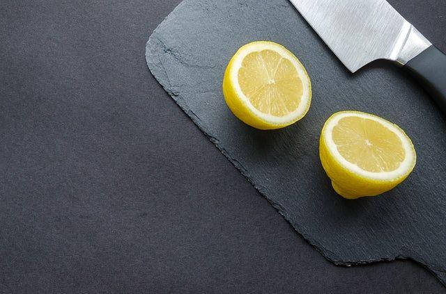 Limone tagliato a metà con il coltello sul tagliere