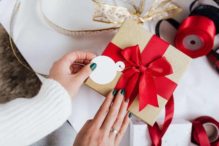 Donna rifinisce un pacchetto regalo con un bel fiocco classico