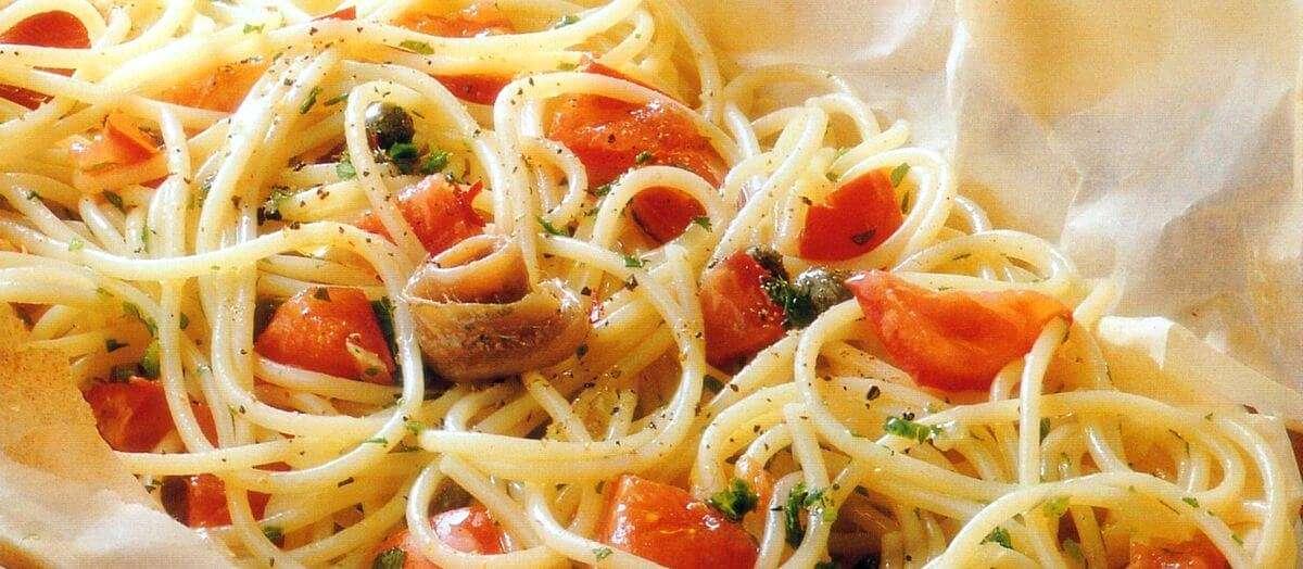 Aspetto degli spaghetti al cartoccio con alici, pomodori, capperi e basilico