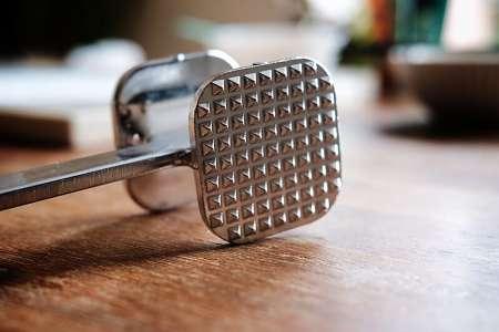 Batticarne di acciaio sul tavolo