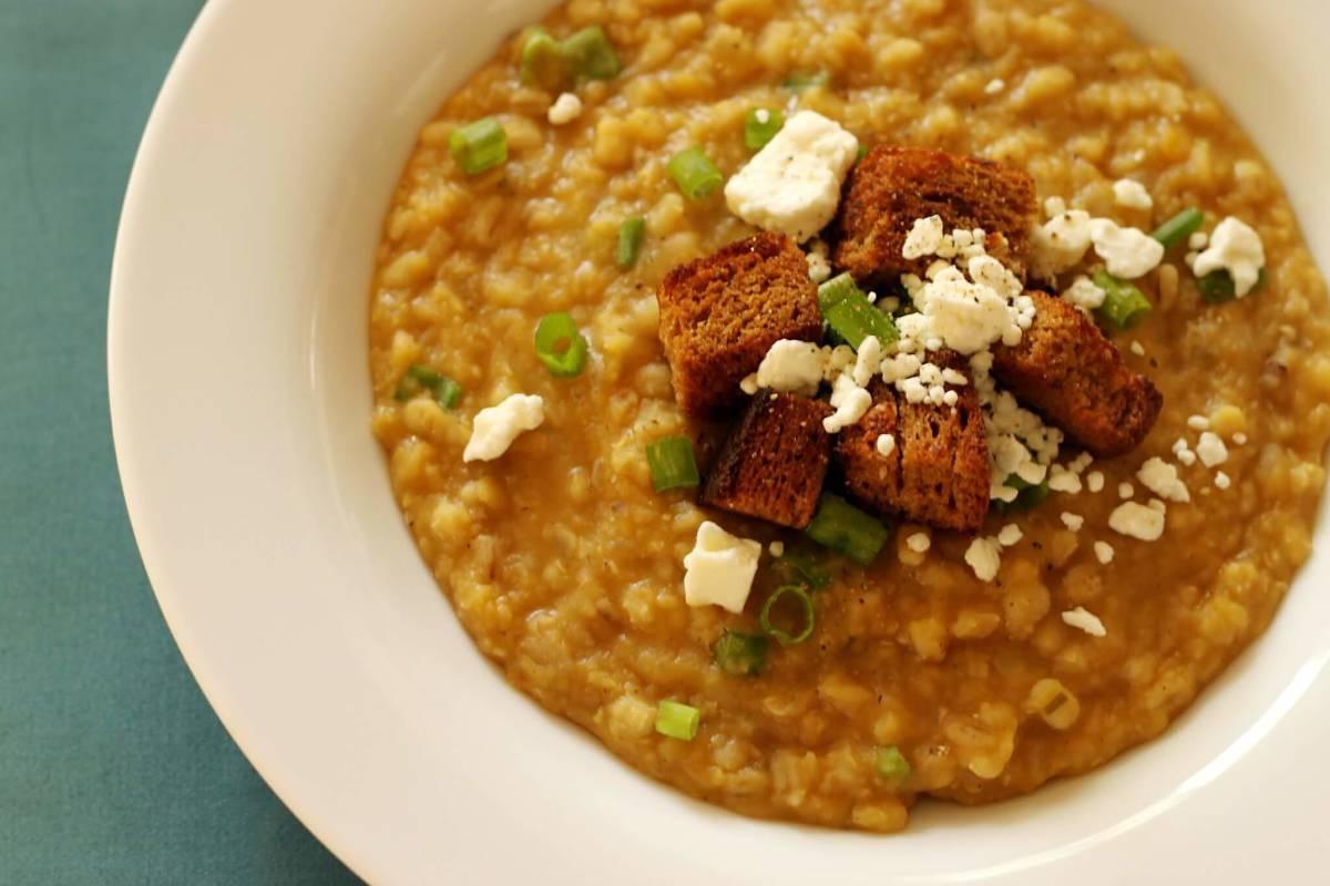 Piatto con zuppa d'orzo e lenticchie rosse con guarnizione di crostini, feta e rondelle di parti verdi di scalogni all'americana