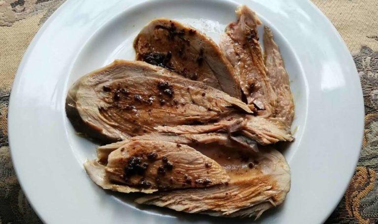 Fette di cosciotto di tacchino con salsina di capperi e olive nel piatto