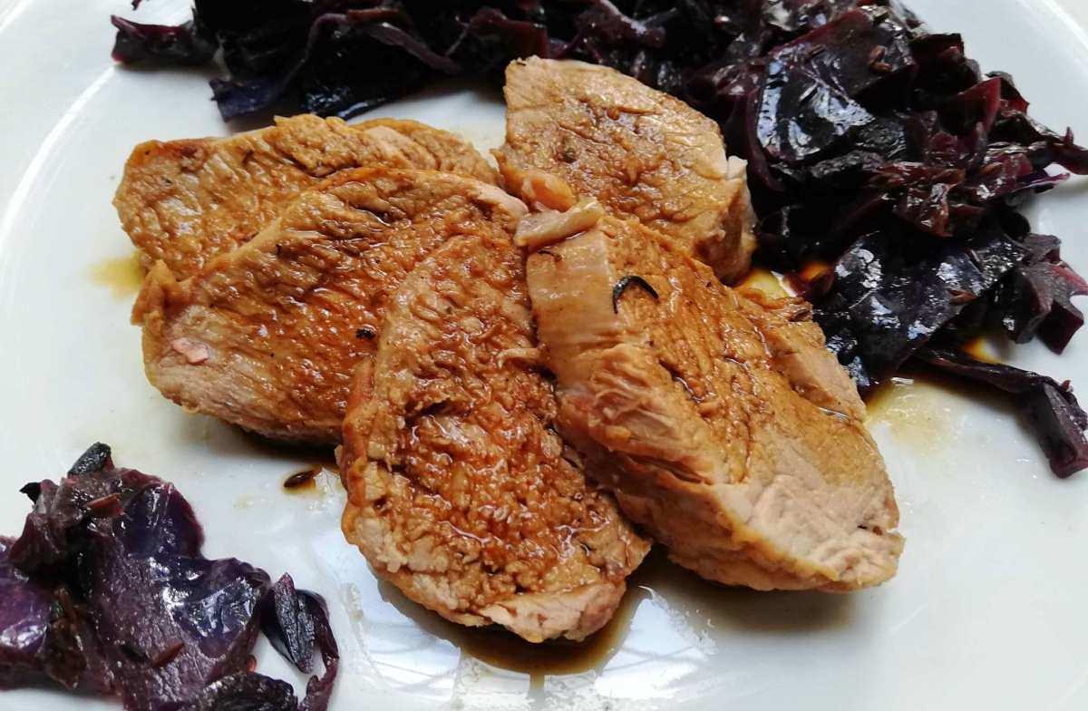 Immagine di arrosto di suino affettato con contorno di cavolo rosso