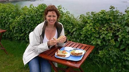 Donna fa un pranzo leggero con sandwich all'aria aperta