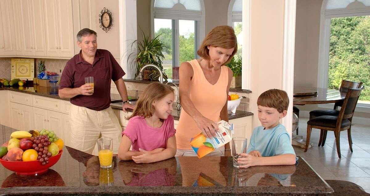 Famiglia riunita attorno al piano di cucina in pietra naturale beve aranciata