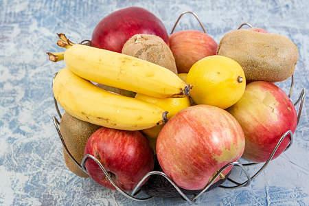 Limoni con mele, banane e kiwi nel portafrutta